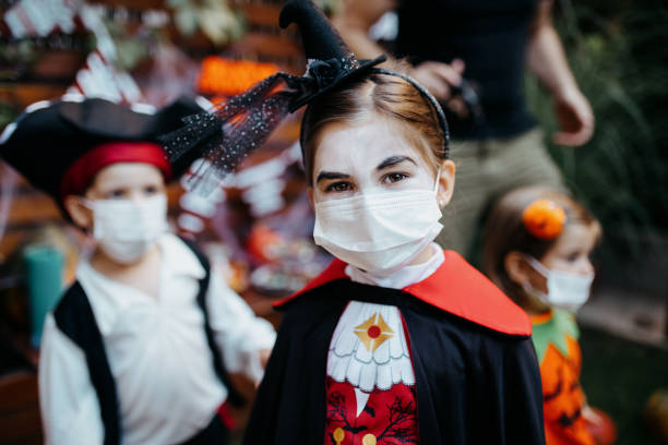 Little kids at a Halloween party Group of kids trick or treating during Covid-19 pandemic wearing face masks halloween covid stock pictures, royalty-free photos & images