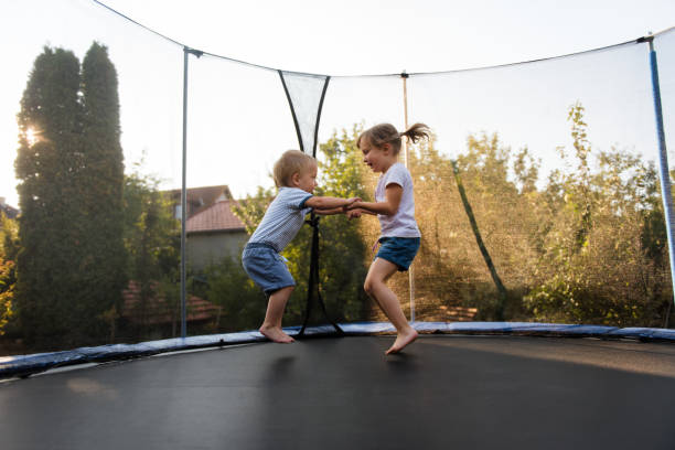 Little kids bouncing off the trampoline taut stock photo