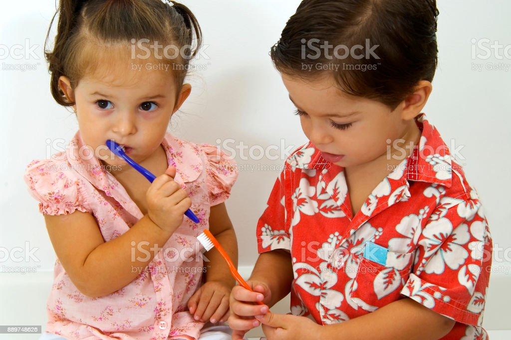 Little kids brushing their teeth stock photo