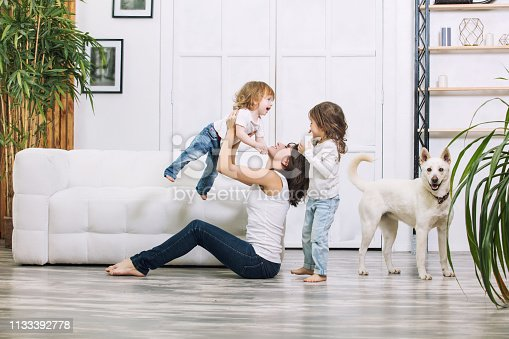 istock Little kids girls are beautiful and cute with mother and pet dog at home together happy 1133392778