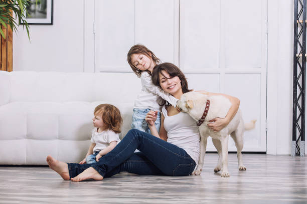 Little kids girls are beautiful and cute with mother and pet dog at home together happy stock photo