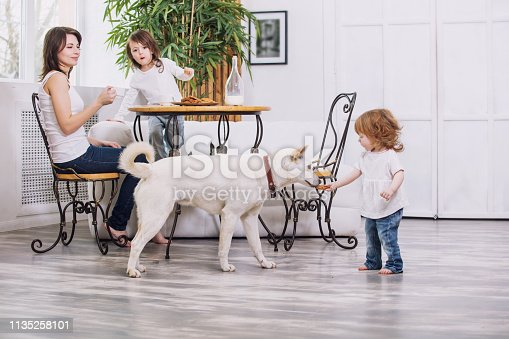 Little kids girls are beautiful and cute with mother and pet dog at home together eating cookies with milk