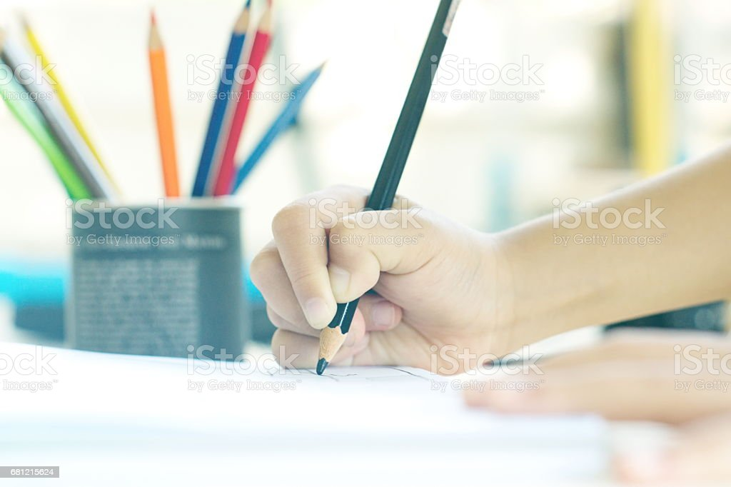 Little kid's hand drawing something on white paper. royalty-free stock photo