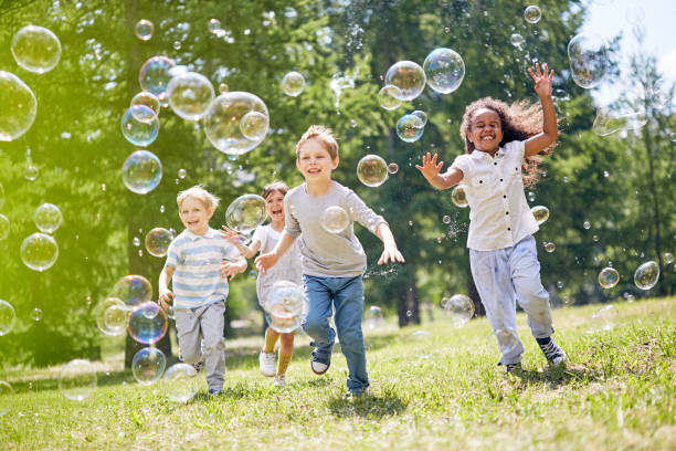 Little Kids Having Fun Outdoors Multi-ethnic group of little friends with toothy smiles on their faces enjoying warm sunny day while participating in soap bubbles show leisure equipment stock pictures, royalty-free photos & images