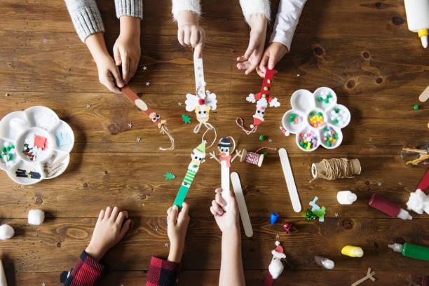 kleine kinder halten weihnachten zeichen verziert popsicle sticks - diy xmas stock-fotos und bilder