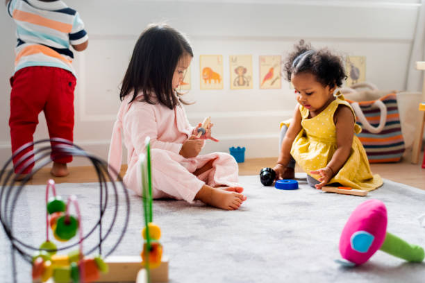 Little kids playing toys in the playroom Little kids playing toys in the playroom preschool age stock pictures, royalty-free photos & images