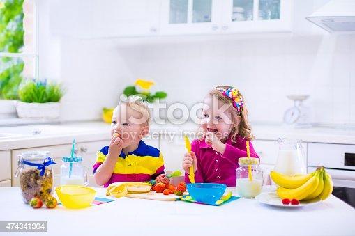 istock Little kids preparing breakfast in a white kitchen 474341304