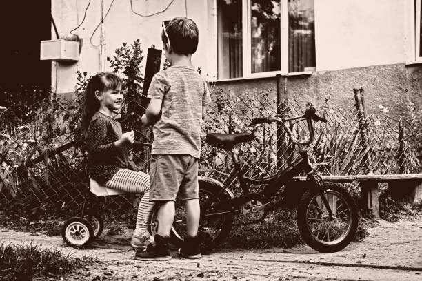 Little kids talk cute about important things. Kids on bikes in retro style stock photo