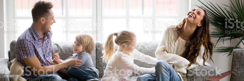 Kleine Kinder kitzeln Eltern Familie mit Spaß sitzen auf der Couch - Lizenzfrei Adoption Stock-Foto