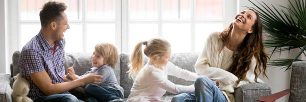kleine kinder kitzeln eltern familie mit spaß sitzen auf der couch - breit stock-fotos und bilder