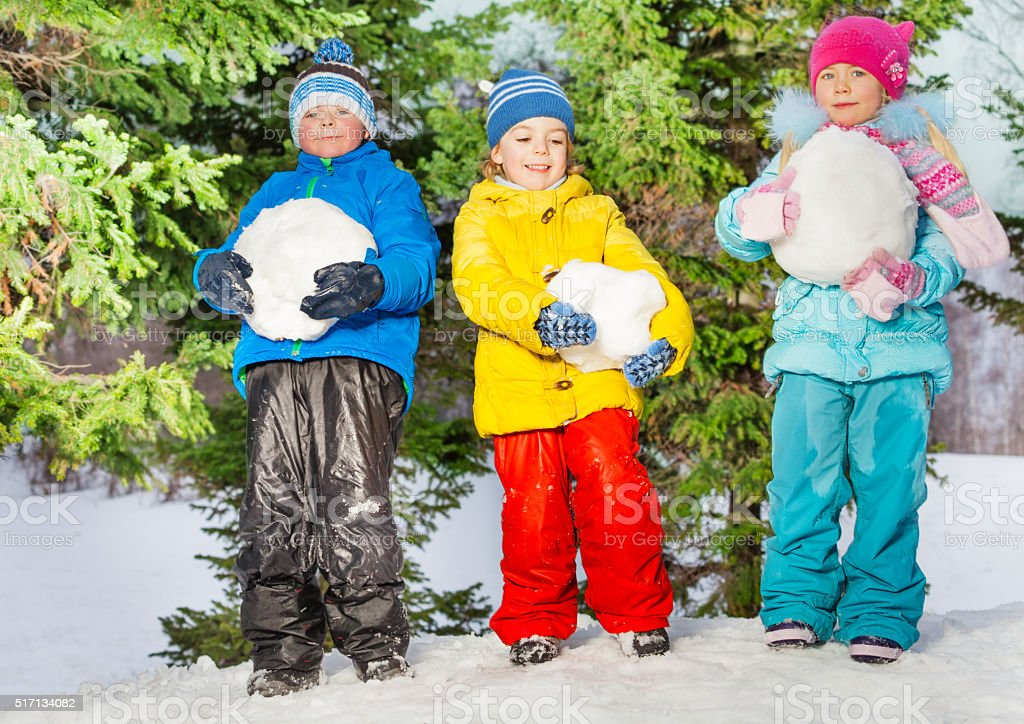 Little kids with big snowballs in the park stock photo