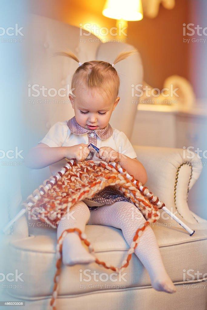 Little knitting girl stock photo
