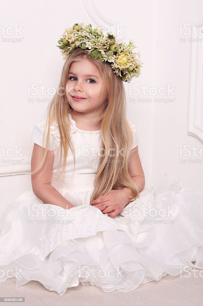 Little lady in dress with head wreath. White background stock photo
