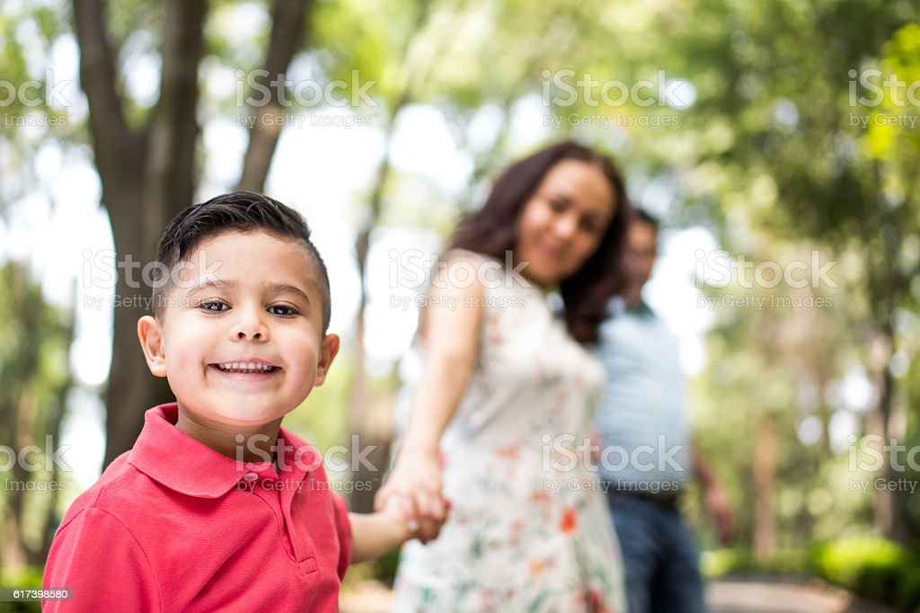 Little latin boy hand in hand with mother and smiling stock photo
