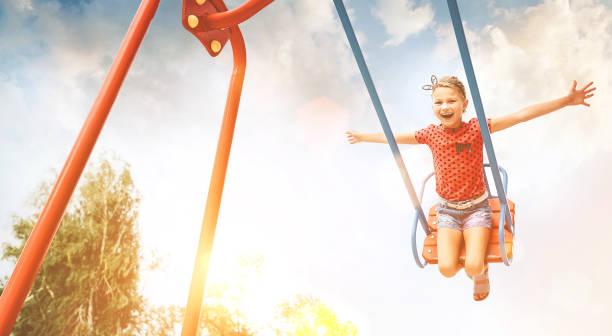 Kleines lachendes Mädchen auf Schaukel Happy Kinder-Kind-Konzept Bild. – Foto