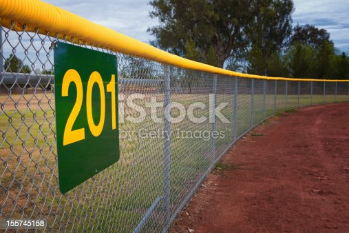 Little league baseball fence with a distance marker sign.