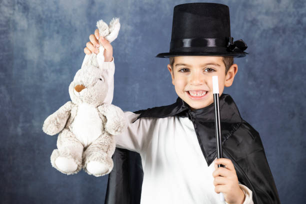 Little magician doing a trick with a rabbit Little magician doing a trick with a rabbit magic trick stock pictures, royalty-free photos & images