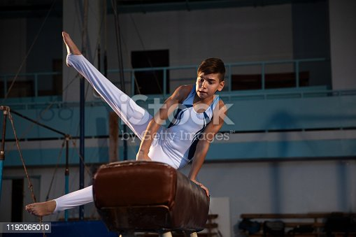 Little male gymnast training in gym, flexible and active. Caucasian fit little boy, athlete in white sportswear practicing in exercises for strength, balance. Movement, action, motion, dynamic concept.