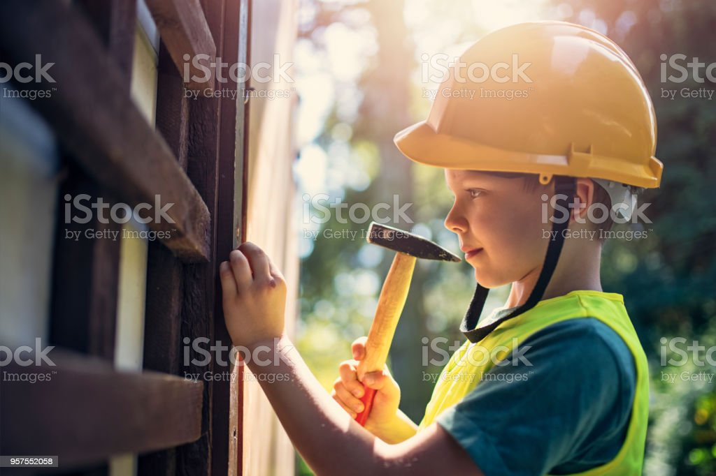 Little manual worker hammering a nail. Little boy is playing in...