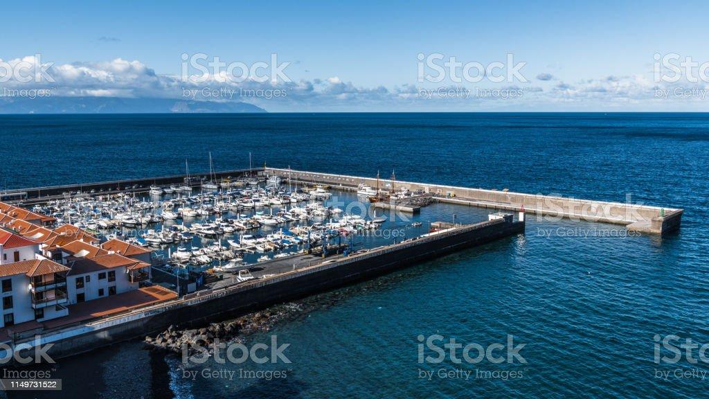 The last rays of the setting sun illuminate the Marina, full of...