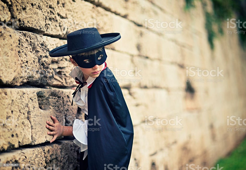 Little masked hero girl sneaking past old wall stock photo