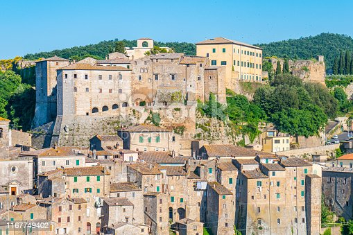 The great little city of Sorano, in province of Grosseto, Tuscany, Italy. Beautiful cityscape on the rock, with woods around the town and blue sky.