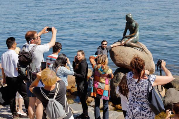 kleine meerjungfrau und touristen - kleine meerjungfrau kunst stock-fotos und bilder