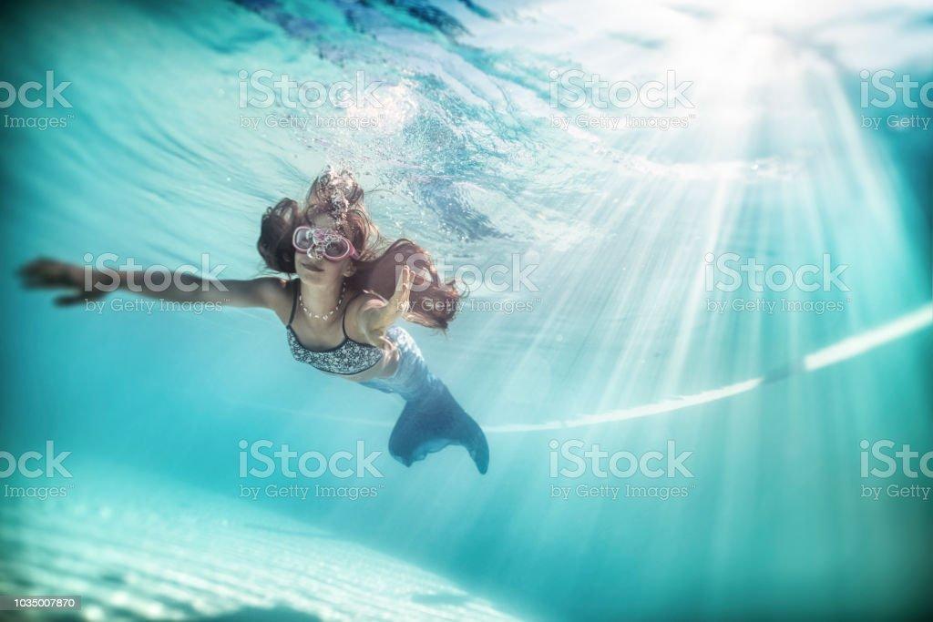 Little mermaid swimming underwater. stock photo