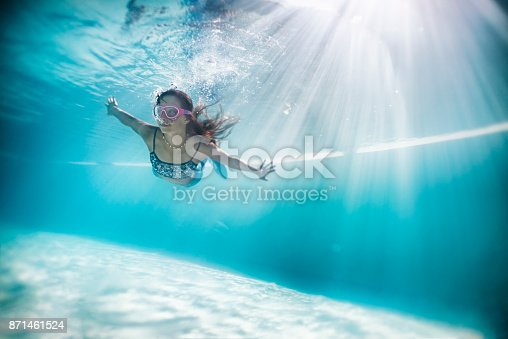 Little marmaid aged 11 is swimming underwater. The mermaid is wearing swimming googles. Not that she needs them, it's just the fashion thing.\n