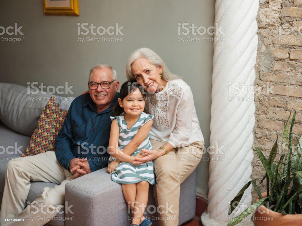 Pequeña chica mexicana sentada con sus abuelos - foto de stock