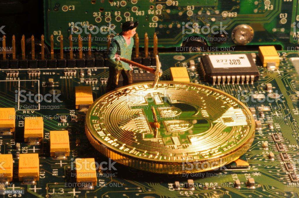 A little miner is digging on electronic graphic card with golden coin. bitcoin mining and crypto currency concept. stock photo