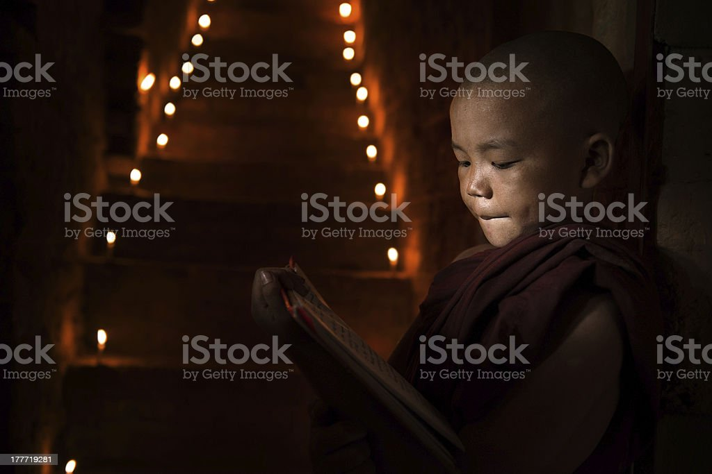 Little monk reading book stock photo