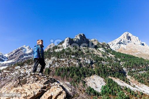 istock Little mountaineer on the peak of the mountains 1090201124