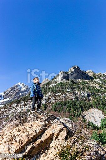 istock Little mountaineer on the peak of the mountains 1090201126