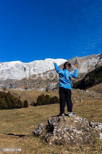 istock Little mountaineer on the peak of the mountains 1090201146