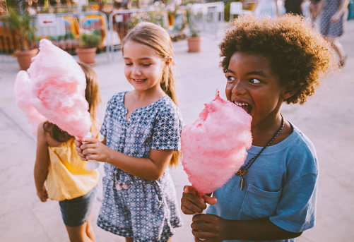 Happy multi-ethnic kids eating pink cotton candy at travelling carnival on summer holidays