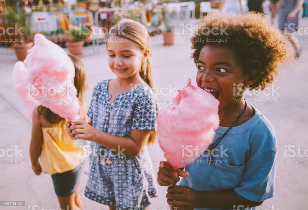 Little multi-ethnic children eating cotton candy at amusement park stock photo