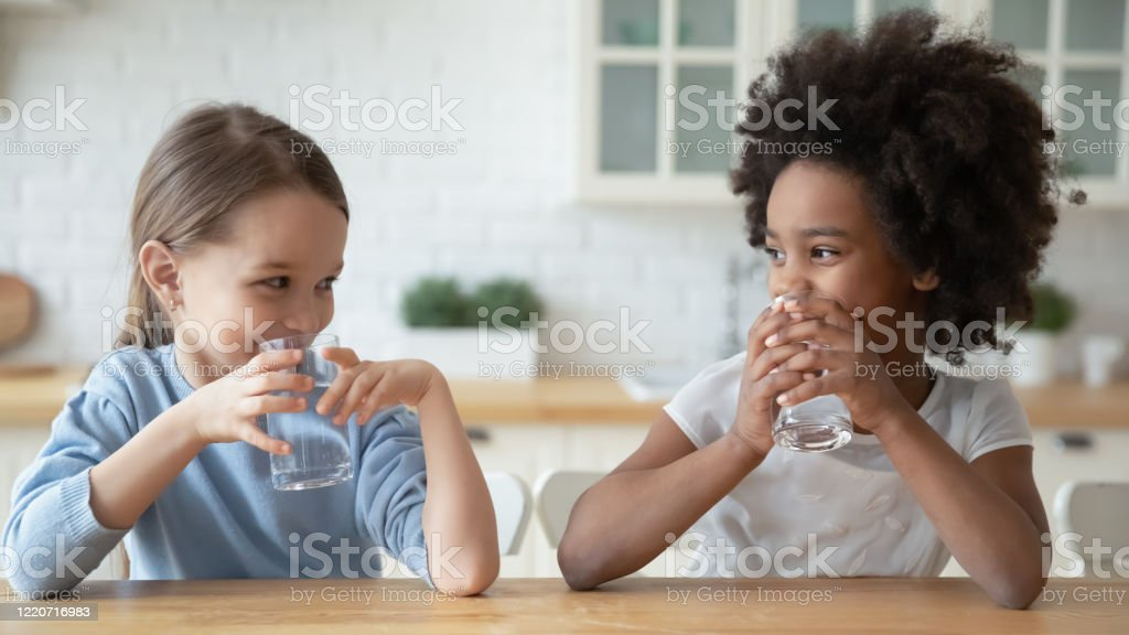 Little multiethnic girls drink mineral water at home Happy little multiracial sisters sit at table in home kitchen drink pure mineral water, smiling small multiethnic girls children enjoy clean still aqua, feel thirsty, healthy lifestyle concept Balance Stock Photo