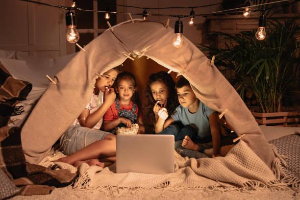 wenig multiethnischen kinder zelt sitzen und beobachtete film zusammen auf laptop - tipi zelt stock-fotos und bilder