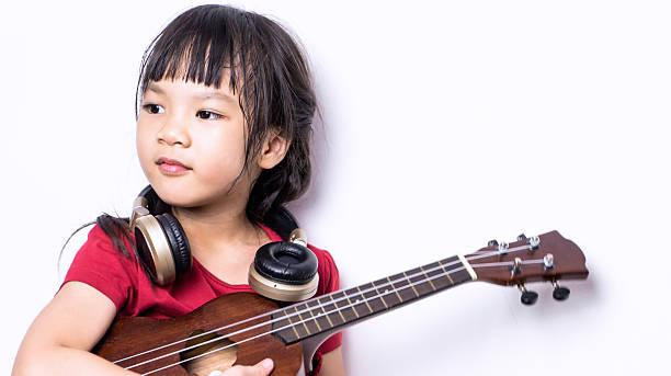 little musician with guitar headphone isolated on white. - ukulele songs stock-fotos und bilder