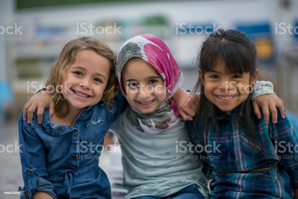 Little Muslim girl and her friends enjoy a day at school together. stock photo
