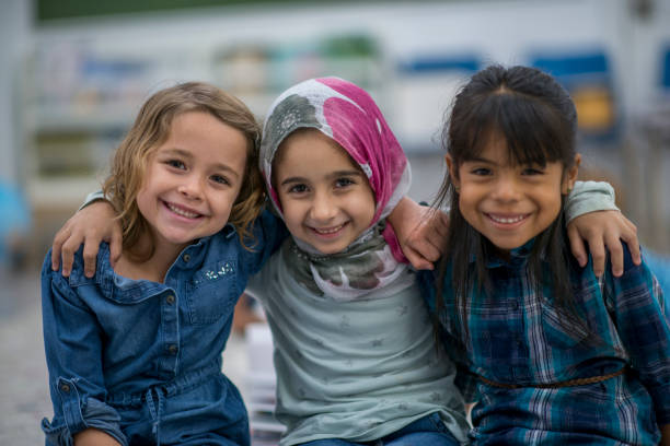 Little Muslim girl and her friends enjoy a day at school together. Little Muslim girl wearing a hijab is enjoying the day at school with her friends. human rights stock pictures, royalty-free photos & images