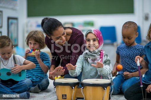 Little Muslim girl wearing a hijab is enjoying playing music with her friends and teacher at school.  She is happy and playing the drums.