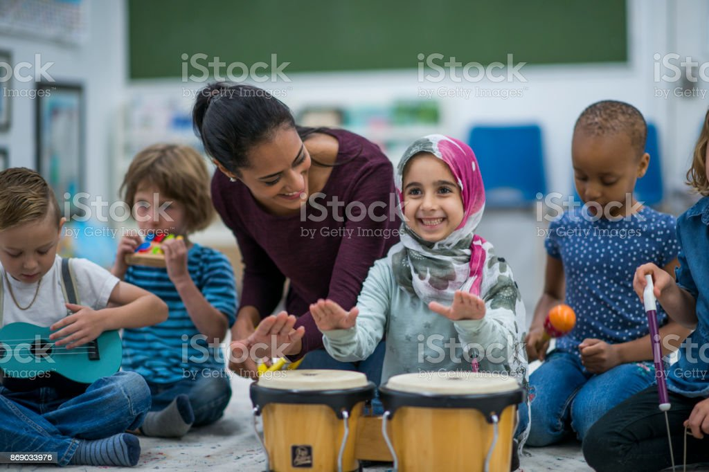 Little Muslim girl enjoy music class at school with her friends. stock photo
