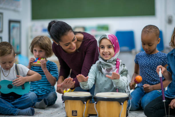 little muslim girl enjoy music class at school with her friends. - preschool stock photos and pictures
