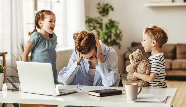 little naughty children distracting busy young woman from work on laptop at home - remote work imagens e fotografias de stock