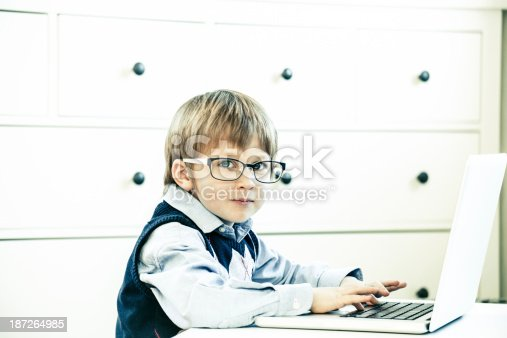 Cute 5 years old Caucasian little boy with nerdy glasses, sitting at a laptop PC, looking at camera
