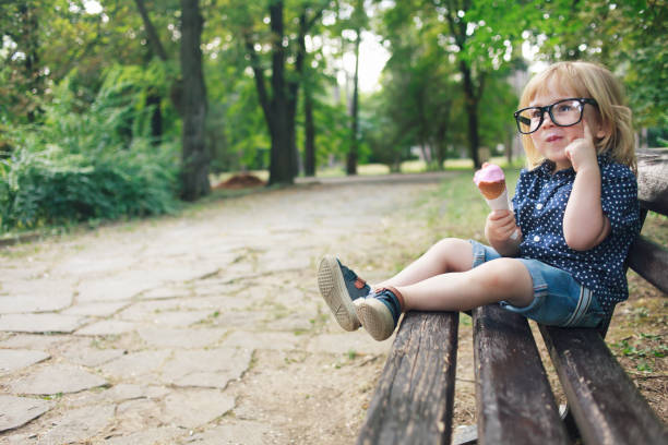 little nerd boy with eyeglasses eating ice cream in a park - nerd boy eating stock photos and pictures