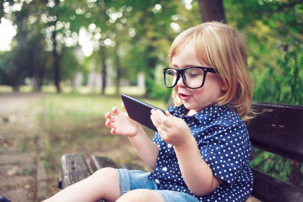 Kleiner Nerd junge mit Brille mit Smartphone – Foto