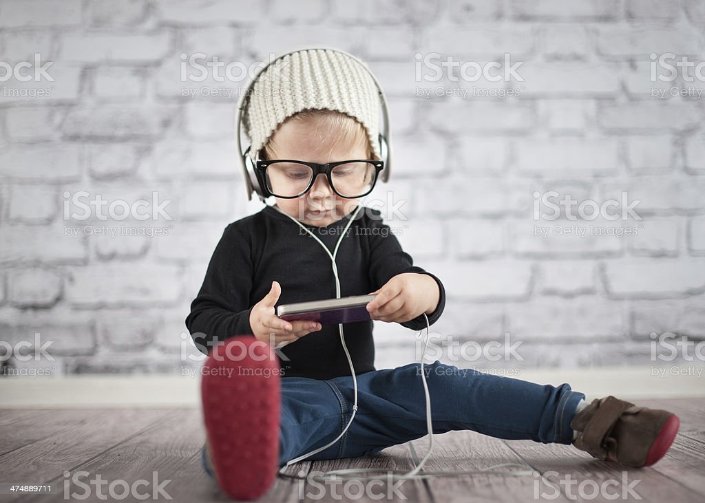 Little nerd with music player stock photo